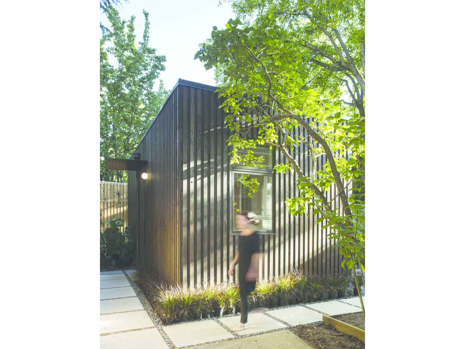 Exterior, House Building Type, Wood Siding Material, and Tiny Home Building Type Light and shadow play on the textured facade.  Greenery frames the simple, geometric form of the house.  Best Photos from A Modern Micro-House in Portland Clad in Local Fir