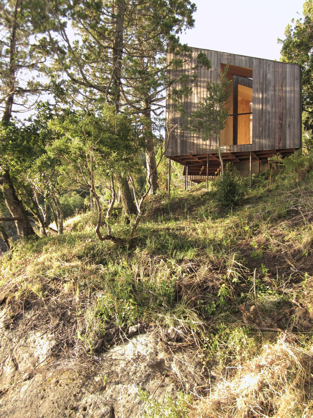 Exterior, House Building Type, and Wood Siding Material Supported on steel supports, the volumes appear to float above the rocks, allowing the natural systems to remain, while blending in between the sky and the ground.  Photo 3 of 9 in A Timber-Clad Sauna in Chile Angles For Lakeside Views