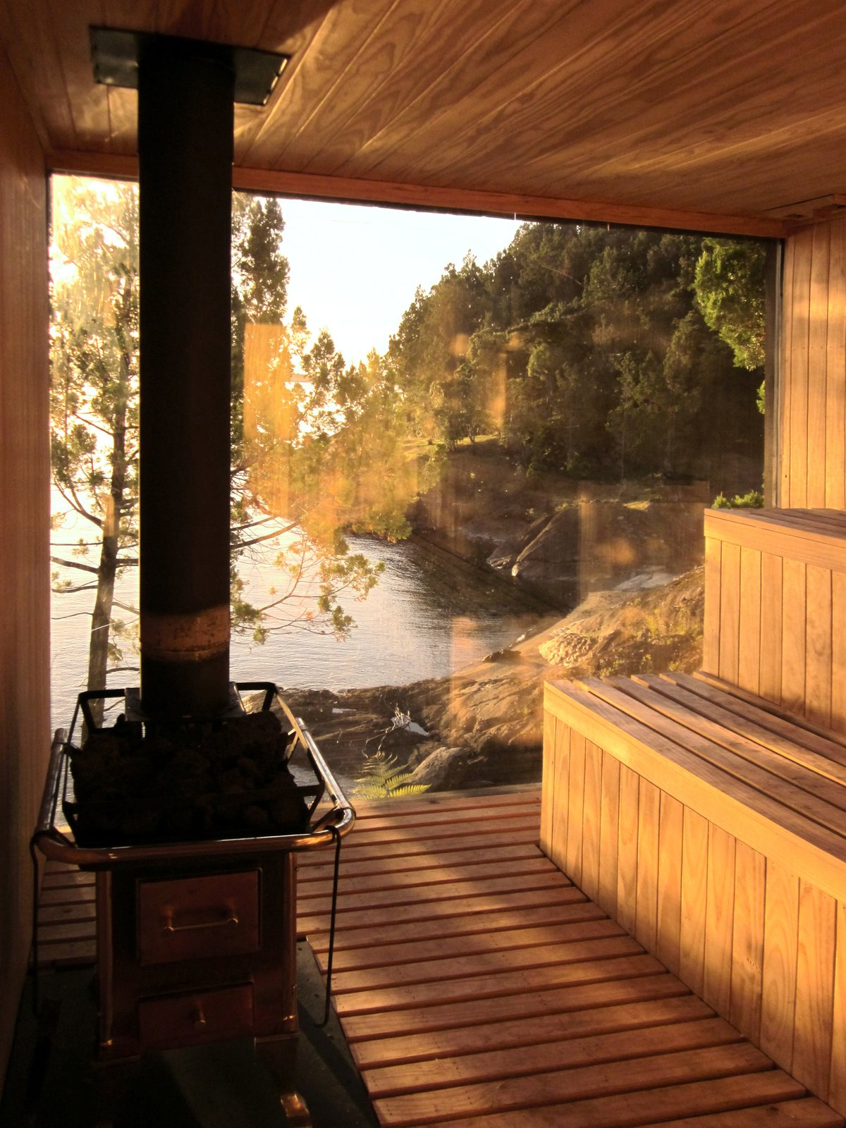 Windows, Picture Window Type, and Wood Encased with wood and glass, surrounded by trees and rocks, the sauna provides a relaxing hideaway for private lake front views.  Photo 6 of 9 in A Timber-Clad Sauna in Chile Angles For Lakeside Views