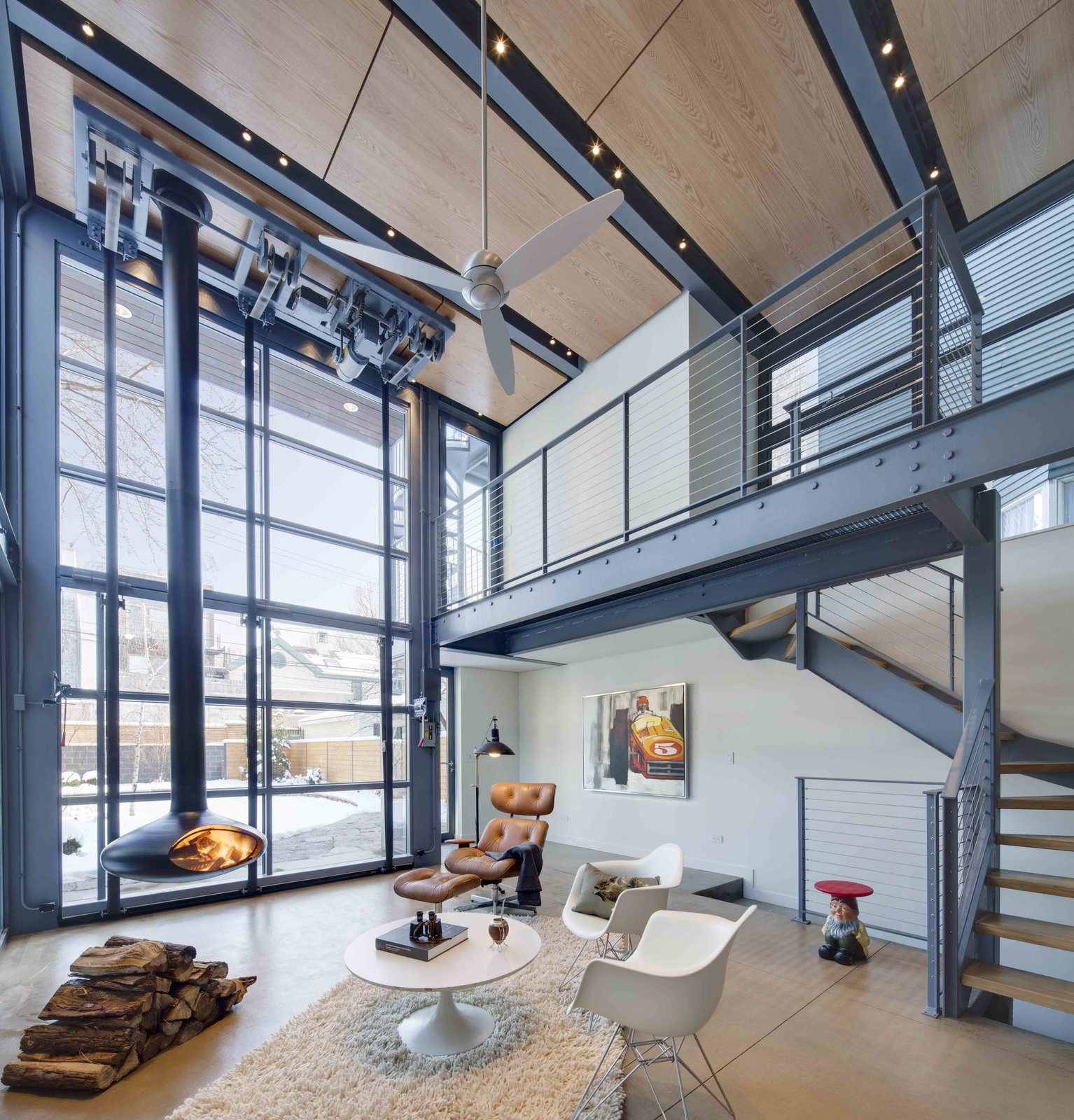 Chair, Coffee Tables, Ceiling Lighting, Concrete Floor, Hanging Fireplace, Metal, Staircase, Wood Tread, and Cable Railing The interior living space is warmed by wood panels above and a hanging fire place.  The large glass hangar provides direct views and connection to the exterior elements.  Living room from A Steel-and-Glass Addition With a Giant Hangar Door Maximizes Indoor/Outdoor Living