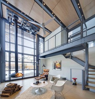 The interior living space is warmed by wood panels above and a hanging fire place.  The large glass hangar provides direct views and connection to the exterior elements.