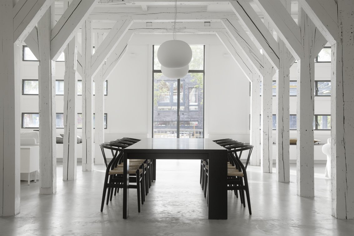 Dining Room, Chair, Table, Pendant Lighting, and Concrete Floor Hans J. Wegner Wishbone Chairs surround the large dining table on axis with the grand, exterior windows.  Best Photos from A Converted Warehouse in Amsterdam Boasts Soothing Interiors of Concrete and Wood