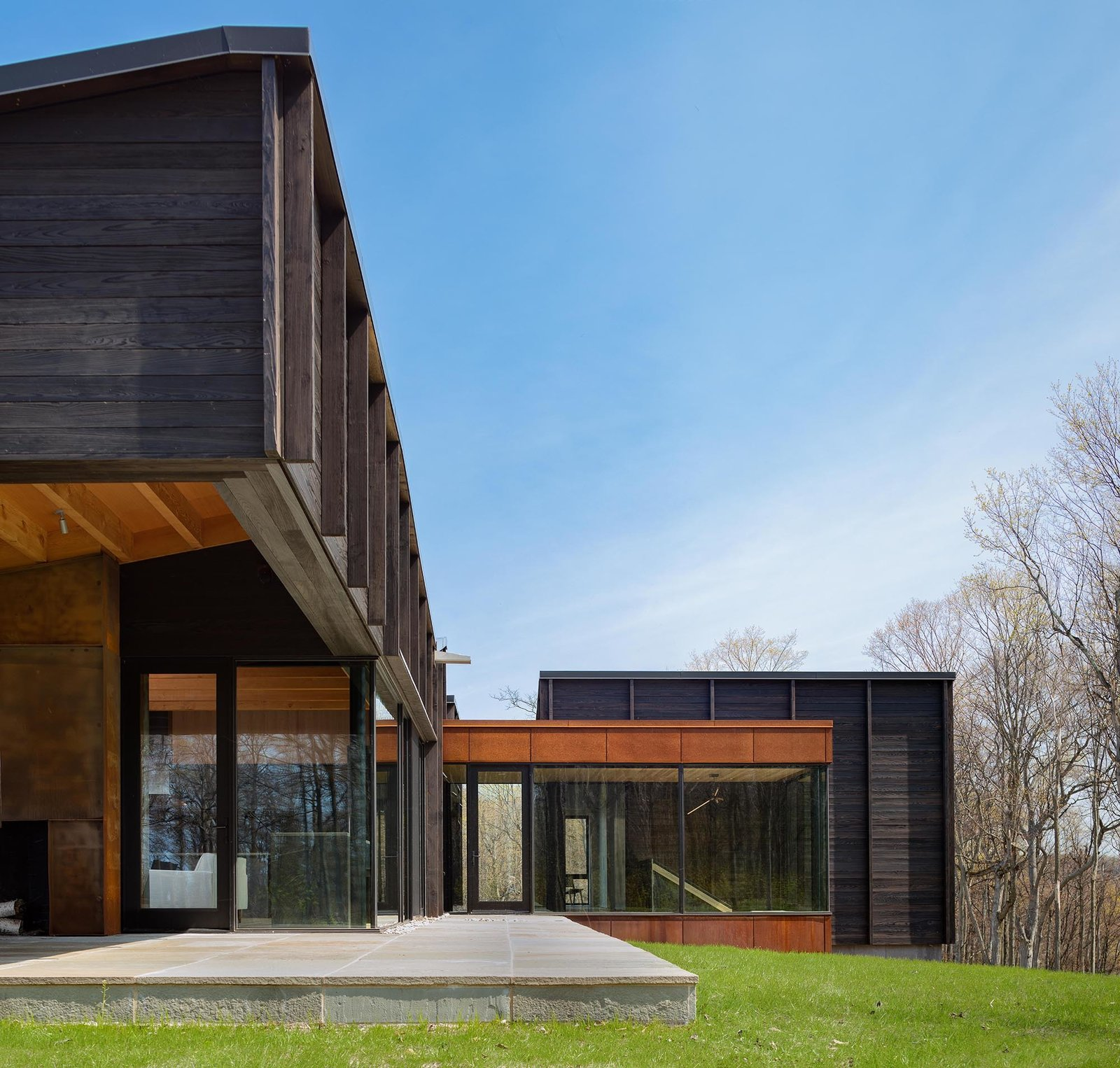 Outdoor, Front Yard, Grass, Hardscapes, and Stone Patio, Porch, Deck The interior living spaces are directly accessible to the exterior terrace.  Photo 2 of 12 in A Dramatic Cantilevered Roof Creates a Spacious Terrace Overlooking Lake Michigan