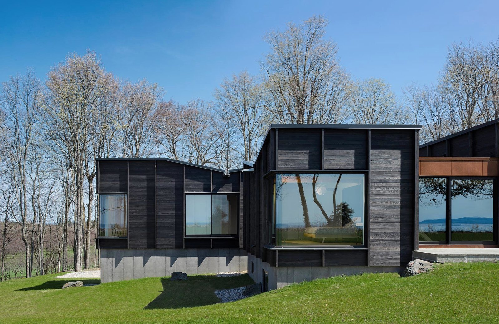 Side Yard, Grass, Trees, Exterior, House Building Type, and Wood Siding Material The two sleeping quarters contain more solid facade than glass to provide adequate privacy.  Best Photos from 1
