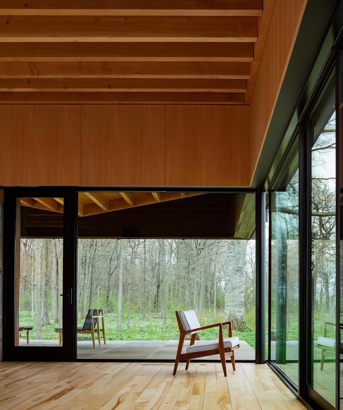 Living Room, Chair, and Light Hardwood Floor Large windows connect the interior to the exterior elements and blend inside to outside.  Photo 6 of 12 in A Dramatic Cantilevered Roof Creates a Spacious Terrace Overlooking Lake Michigan
