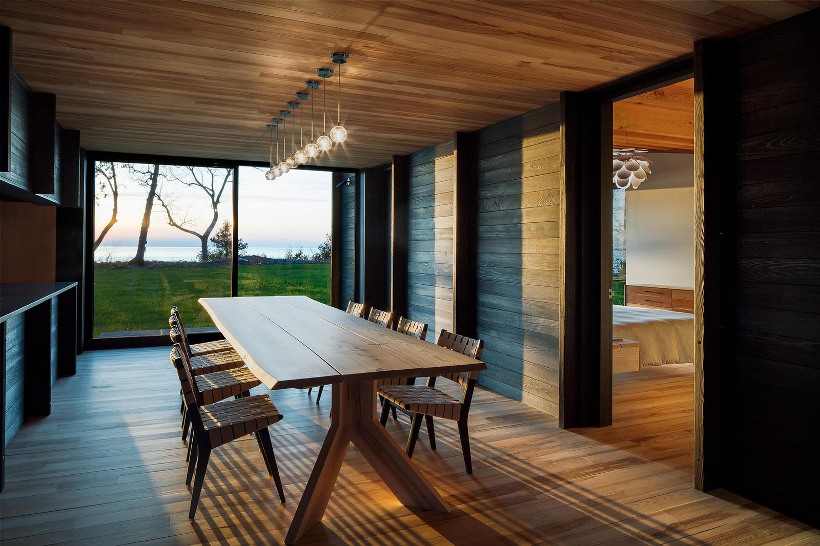 Dining Room, Chair, Table, Ceiling Lighting, Pendant Lighting, and Light Hardwood Floor The dining space, with glass on one end, connects the sleeping quarts with the main living spaces.  Photo 8 of 12 in A Dramatic Cantilevered Roof Creates a Spacious Terrace Overlooking Lake Michigan