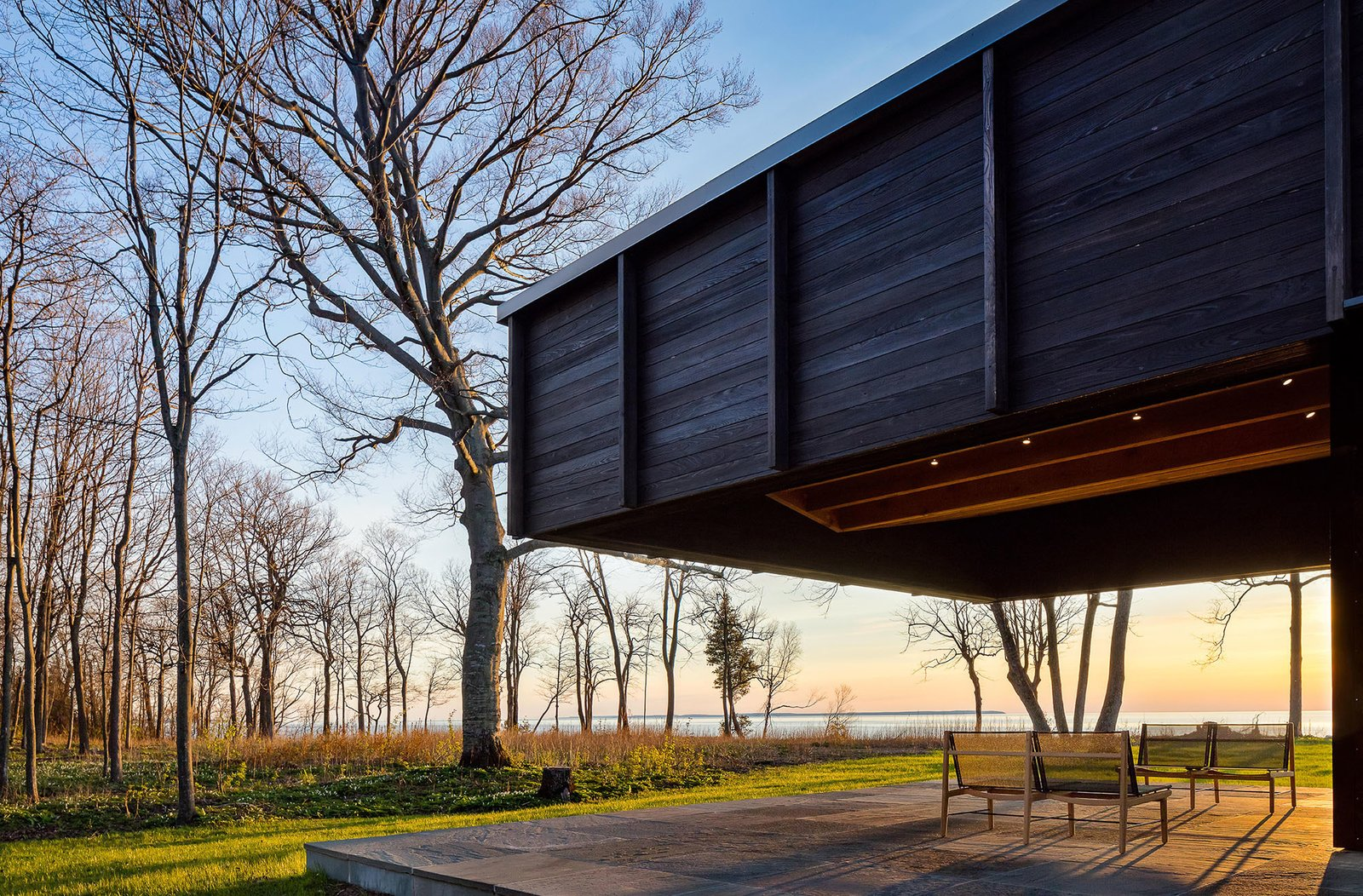 Outdoor, Hardscapes, Grass, Trees, Stone Patio, Porch, Deck, and Woodland The dramatic cantilever provides shade and protection, while leaving views to the lake plentiful.  Photo 11 of 12 in A Dramatic Cantilevered Roof Creates a Spacious Terrace Overlooking Lake Michigan