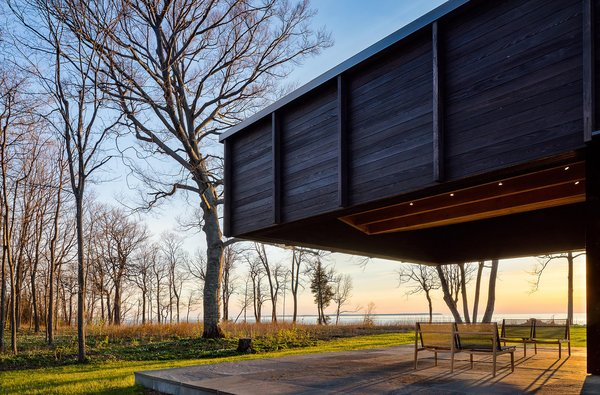 Outdoor, Hardscapes, Grass, Trees, Stone, and Woodland The dramatic cantilever provides shade and protection, while leaving views to the lake plentiful.  Best Outdoor Woodland Stone Photos from A Dramatic Cantilevered Roof Creates a Spacious Terrace Overlooking Lake Michigan