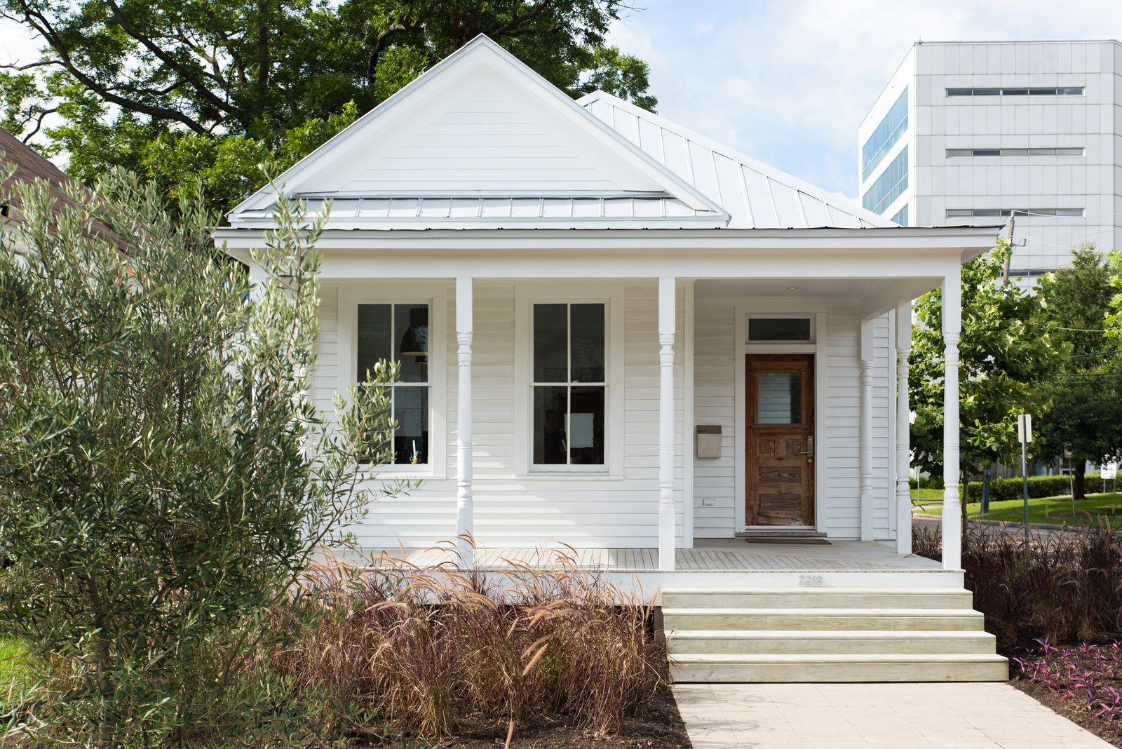 Exterior, House Building Type, Metal Roof Material, and Wood Siding Material Renovated front facade of the home.  Photo 6 of 14 in A Victorian Cottage in Houston Finds New Life as a Local Firm's Office
