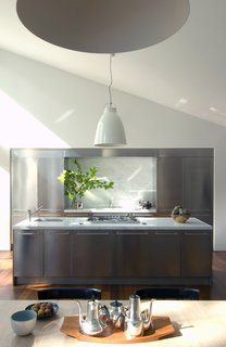 The kitchen sits as a modern insert in the open living space.