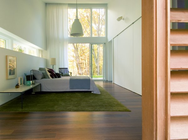 Large windows continue into the master bedroom.  A green rug connects the colors of the exterior with the interior space.
