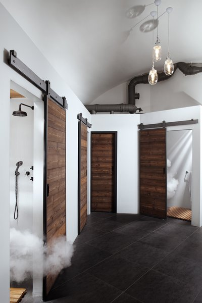 Sliding wood barn doors conceal shower rooms.