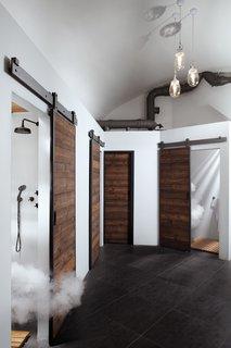 Sliding wood barn doors conceal shower rooms.