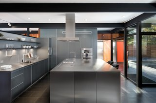 The kitchen, centrally located as the center of activity in the plan, acts as a hinge space, separating more the more formal living and dining spaces from the more casual pool and family room.