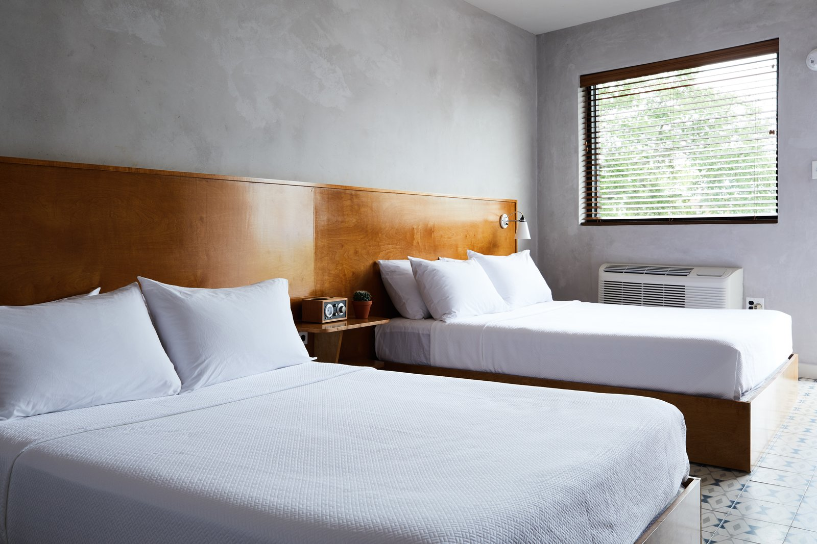 Bedroom, Bed, Night Stands, Wall Lighting, and Ceramic Tile Floor The Double Queen Guest Room's minimalist interiors include a custom, double platform bed, ceramic tile floors, and troweled concrete walls.  Photo 7 of 11 in This Revived New Orleans Motel Has Some Serious Flair