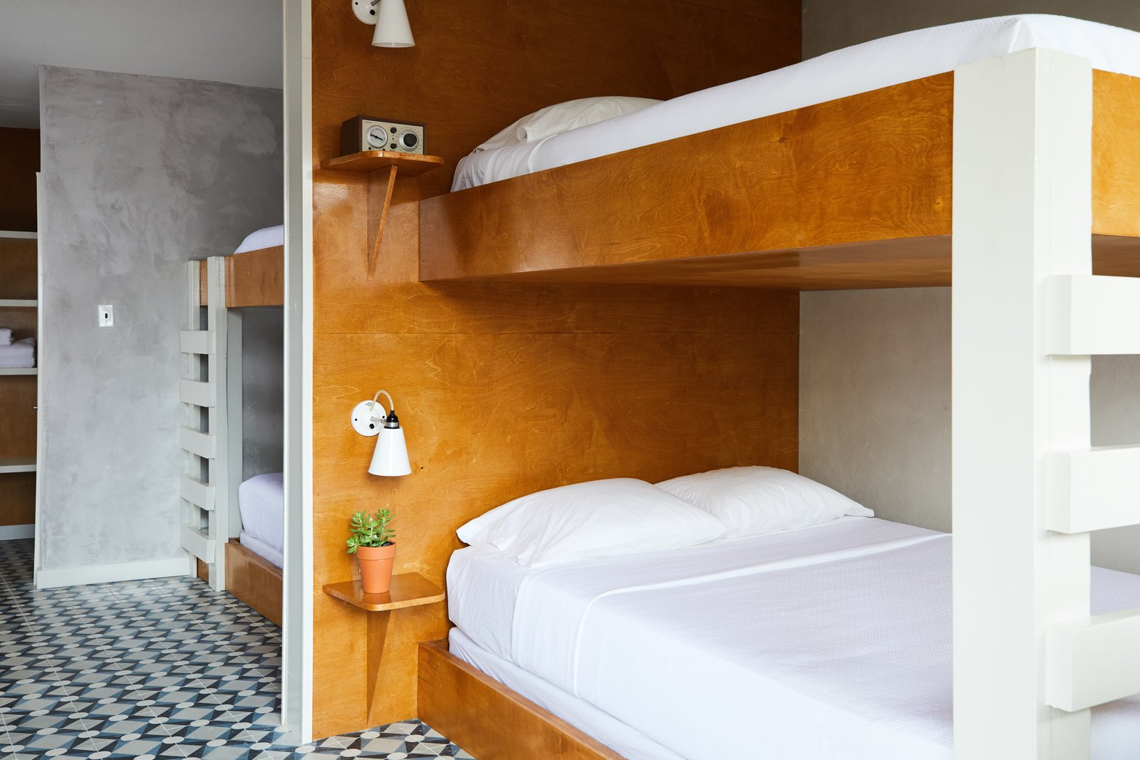 Bedroom, Bunks, Night Stands, Wall, and Ceramic Tile The Bunk Room, located on the first floor, has direct pool access.  Custom built in bunk beds provide the perfect accommodations for a group of friends.  Bedroom Wall Ceramic Tile Photos from This Revived New Orleans Motel Has Some Serious Flair