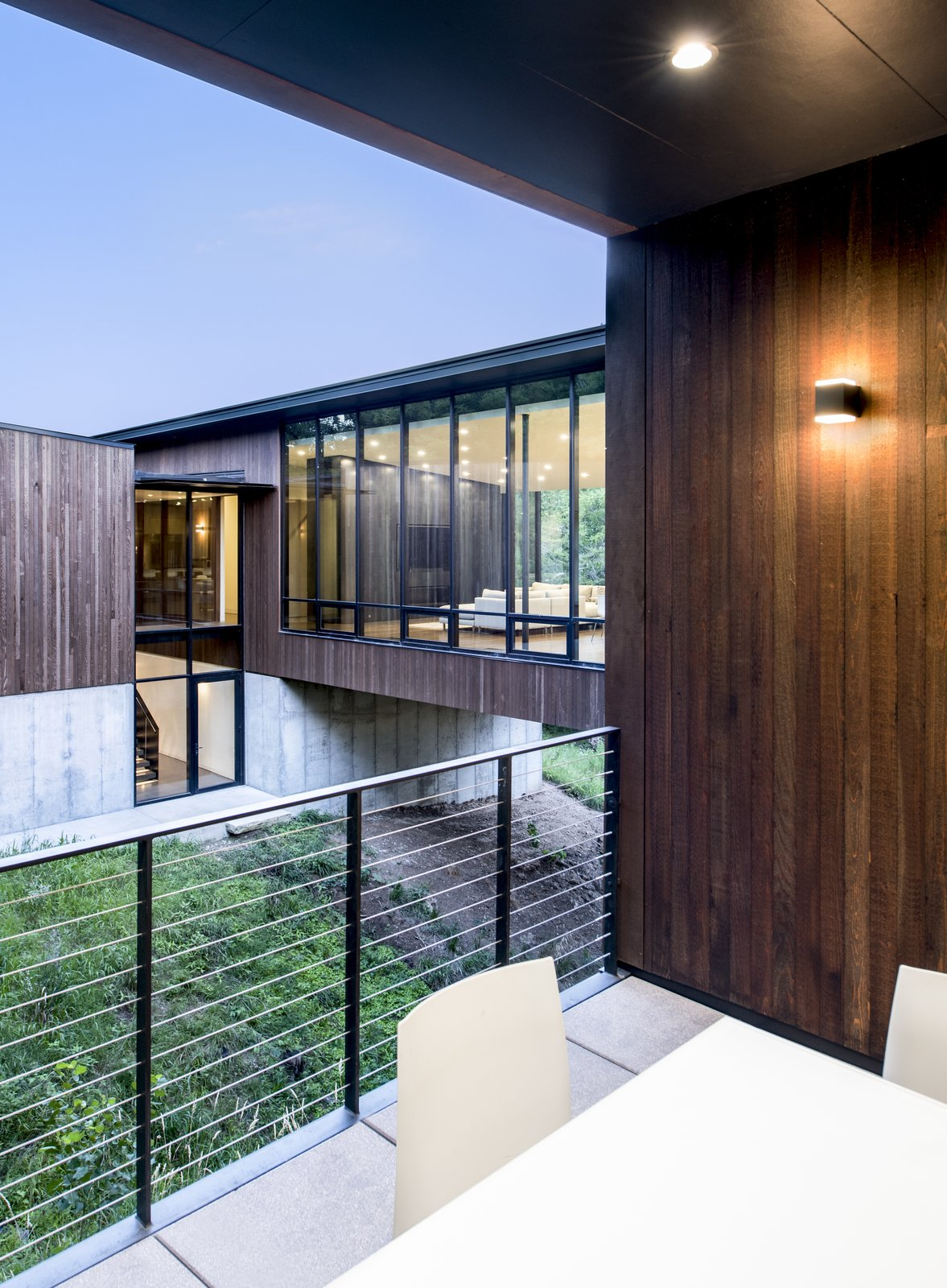 Outdoor and Small Patio, Porch, Deck Despite the large amounts of glass, the organization of the house creates spaces of refuge.  The outdoor patio is nestled into the hillside, sheltered by landscape and building.  Photo 5 of 10 in An Incredible Forest Home Leaps Over a Ravine