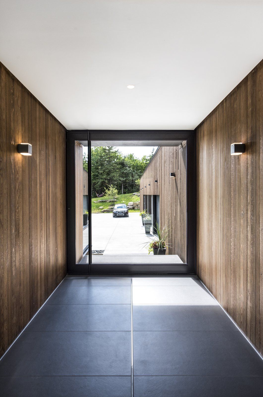 Hallway Cedar walls and Bega wall sconces seamlessly extend from exterior to interior.  Photo 3 of 10 in An Incredible Forest Home Leaps Over a Ravine