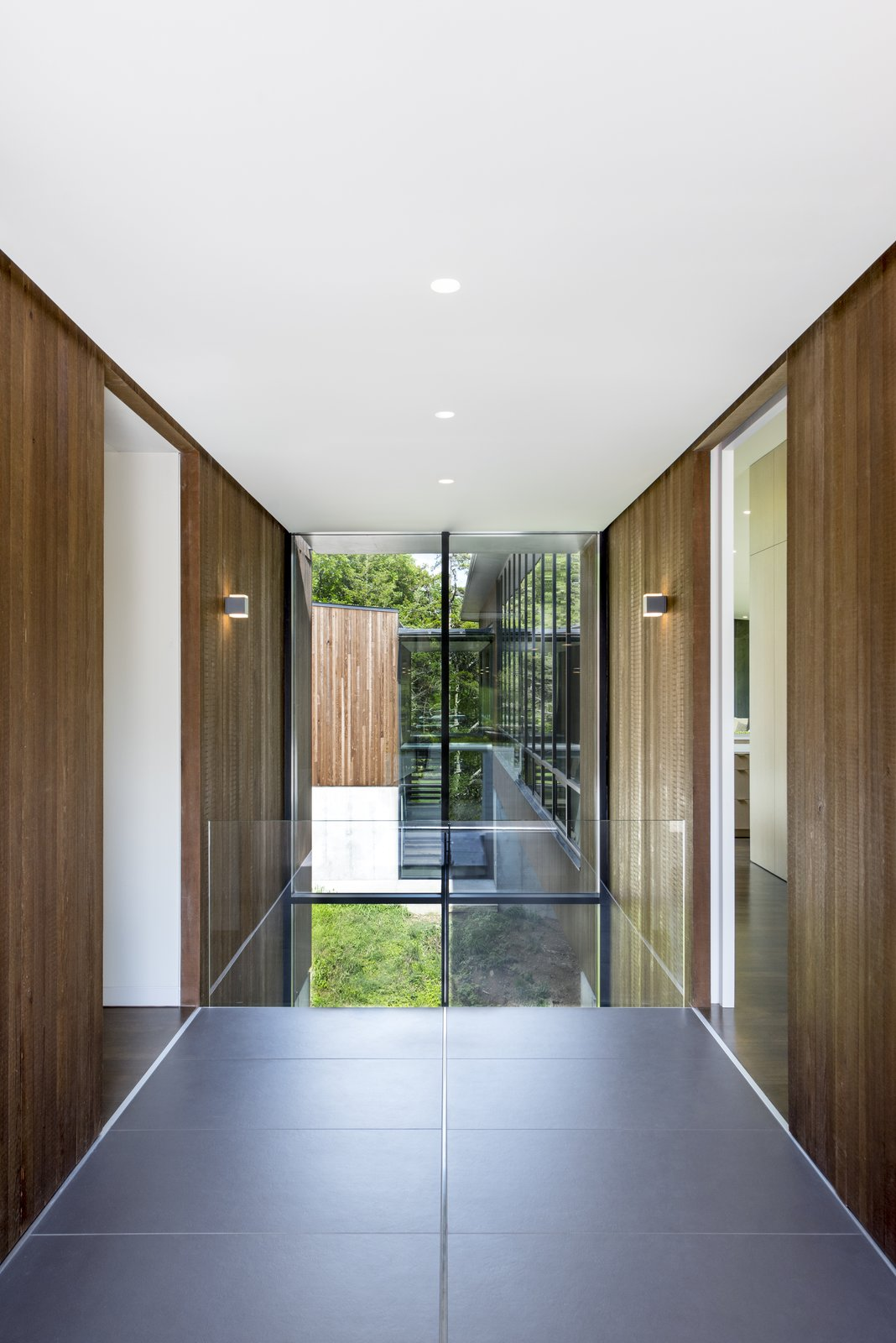 Windows and Picture Window Type Large format Fiandre floor tiles fill the entry sequence and align with the building module.  Photo 4 of 10 in An Incredible Forest Home Leaps Over a Ravine