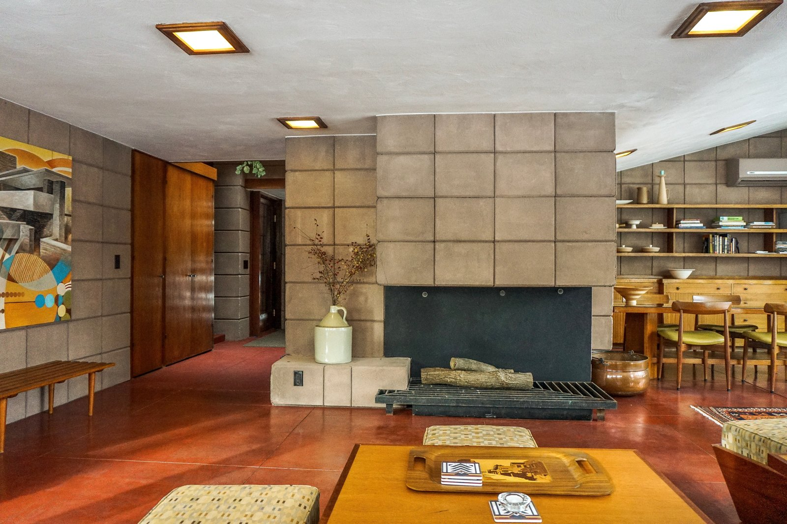 Living Room, Ceiling Lighting, Standard Layout Fireplace, Concrete Floor, Ottomans, Bench, Coffee Tables, and Wood Burning Fireplace Living and dining spaces wrap around the full-height fireplace.  Original light fixtures remain and have been outfitted with LED lights.  Frank Lloyd Wright's Eppstein House from You Can Now Rent Frank Lloyd Wright's Gloriously Restored Eppstein House