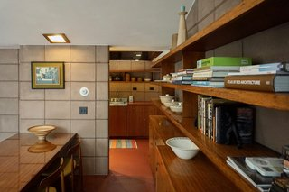 Built-in shelving full of architecture and design books extend from the dining space to the kitchen.