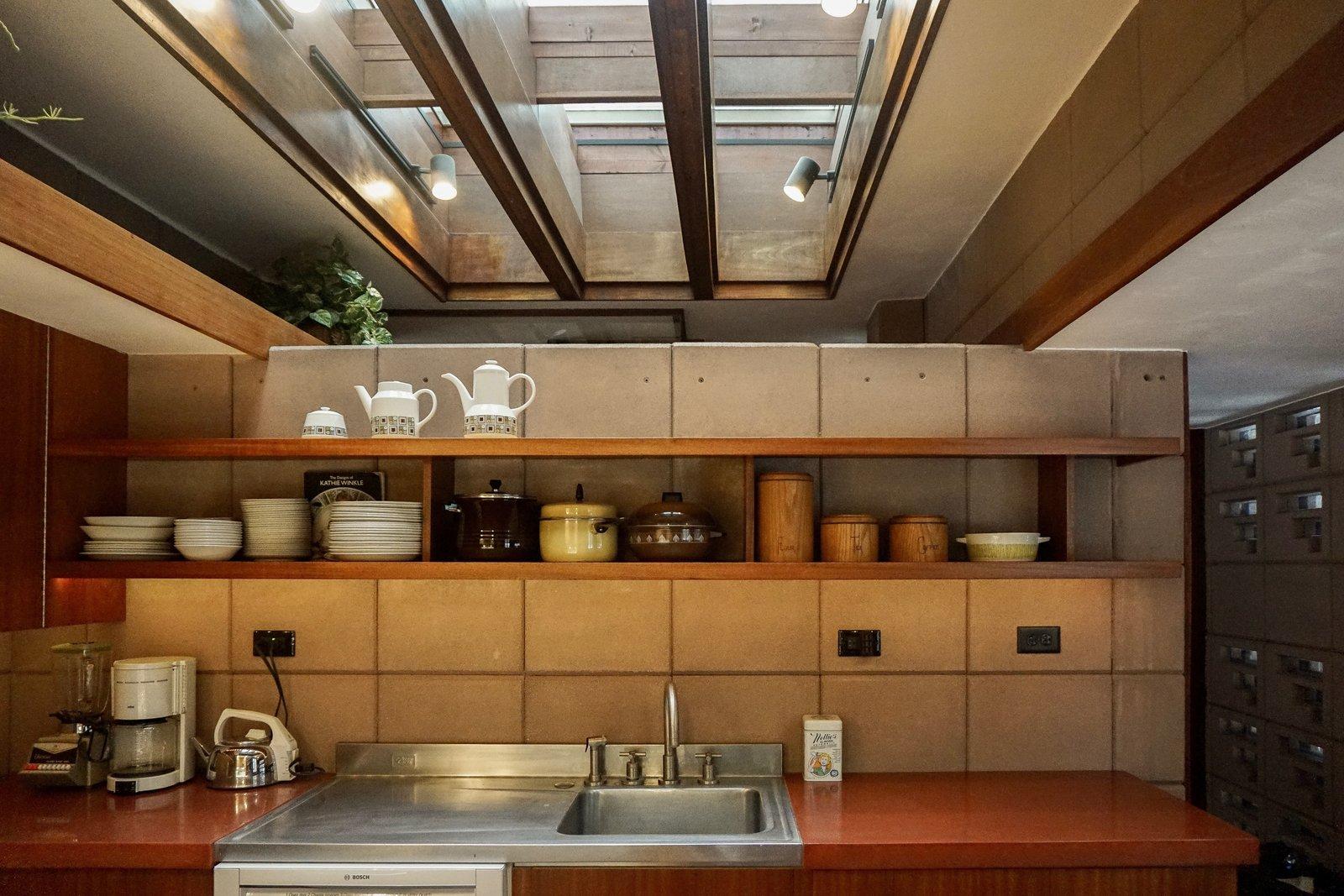 Kitchen, Concrete Backsplashe, Track Lighting, Drop In Sink, And Open  Cabinet Open