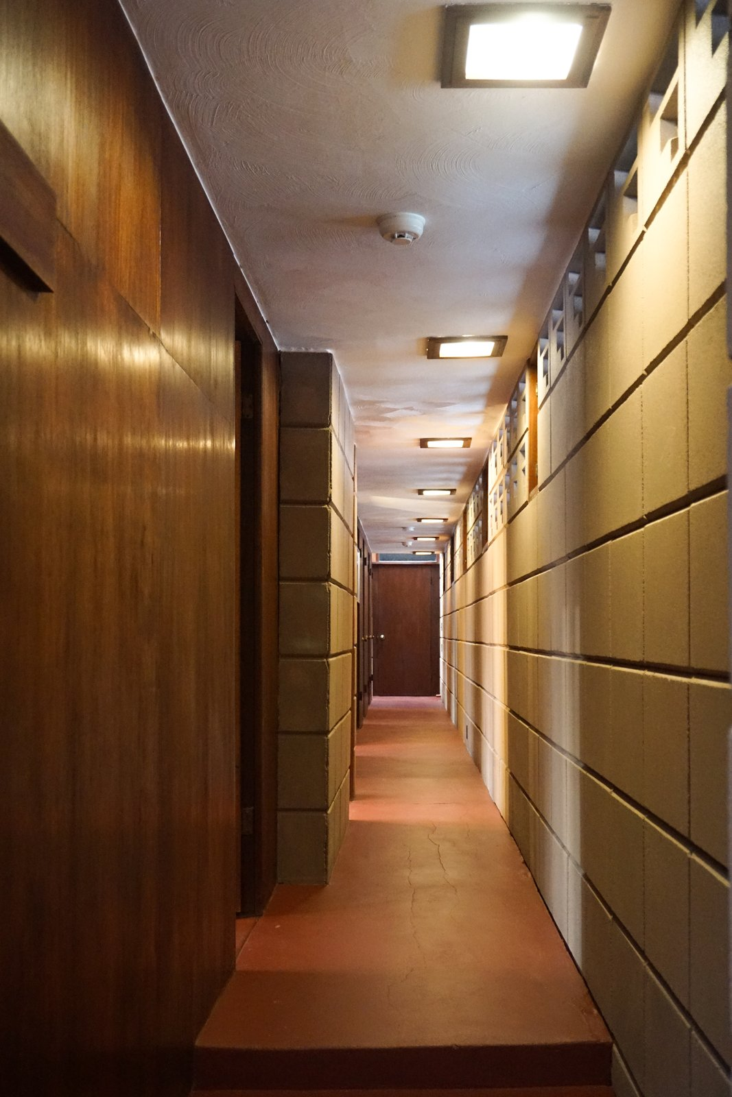 Hallway and Concrete Floor Refinished concrete floors extend down the Gallery corridor.  Perforated concrete blocks act as transom windows to fill the corridor with light.  Mahogany woodwork and doors lead to the sleeping spaces.  Frank Lloyd Wright's Eppstein House from You Can Now Rent Frank Lloyd Wright's Gloriously Restored Eppstein House