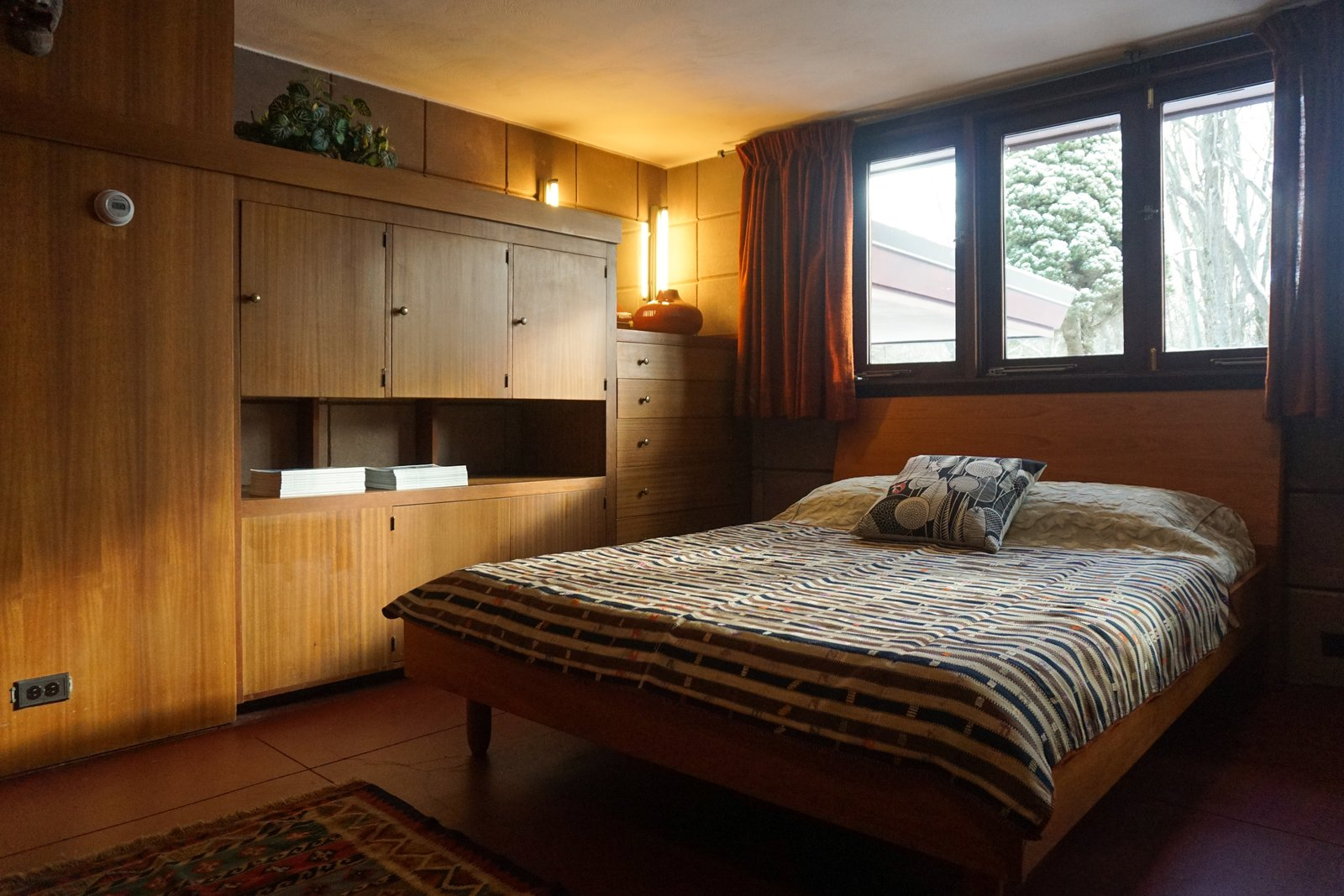Bedroom, Bed, Concrete Floor, Storage, Dresser, Rug Floor, and Wall Lighting Built-in millwork provides ample storage in the bedroom spaces.  Danish teak beds with mid-century textiles resemble the original furnishings.  Frank Lloyd Wright's Eppstein House from You Can Now Rent Frank Lloyd Wright's Gloriously Restored Eppstein House