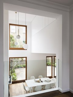 Large windows fill the main living and dining space with natural light.  FLOS IC Pendant Lights hang in the double height space.
