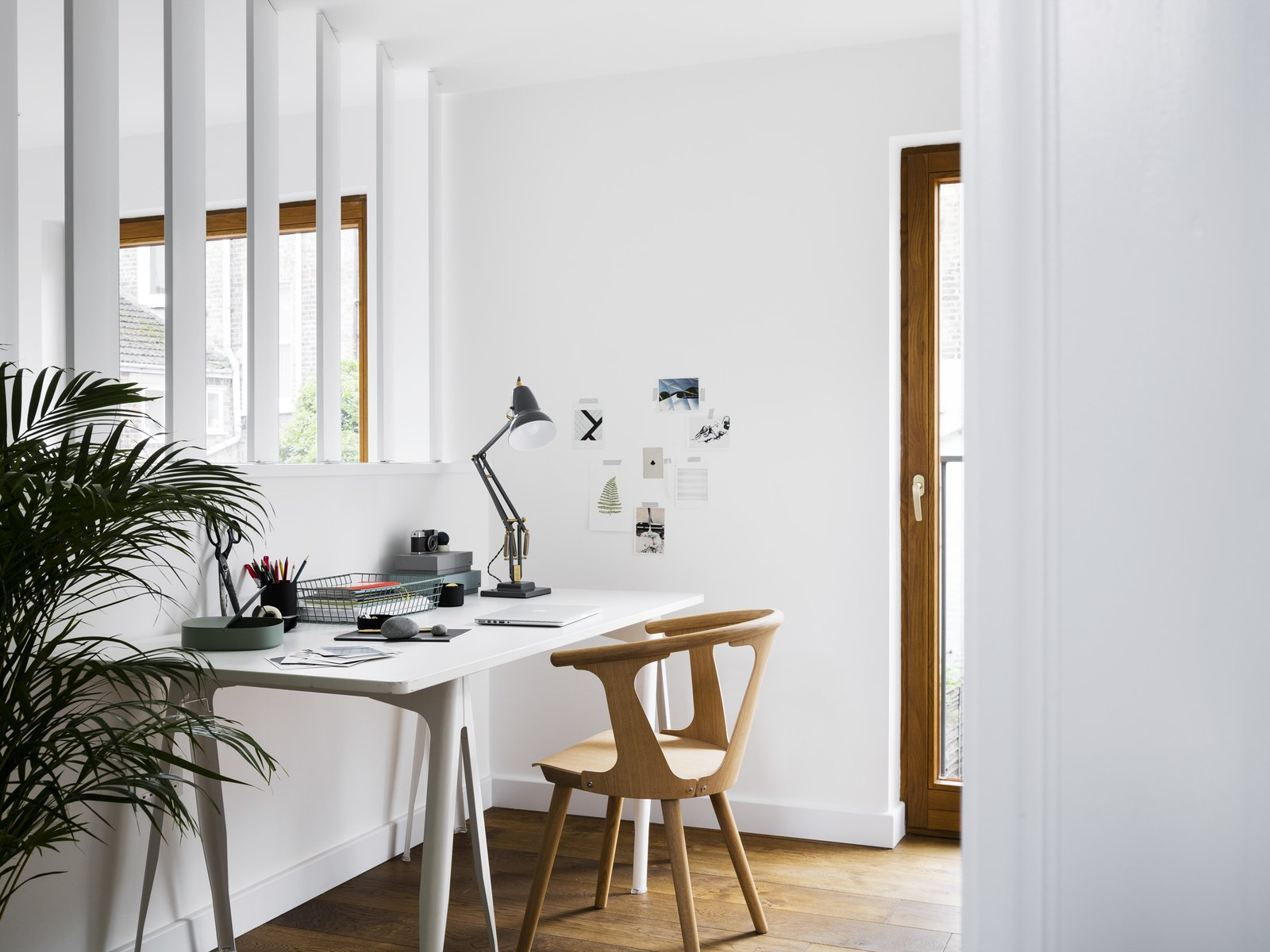 An IKEA desk and SKI wooden provide working accommodations in the study, overlooking the main living space. Tagged: Office, Study, Chair, Desk, Lamps, and Medium Hardwood Floor.  Photo 3 of 11 in A Sleek Renovation in London Ushers Light Into a Family Home
