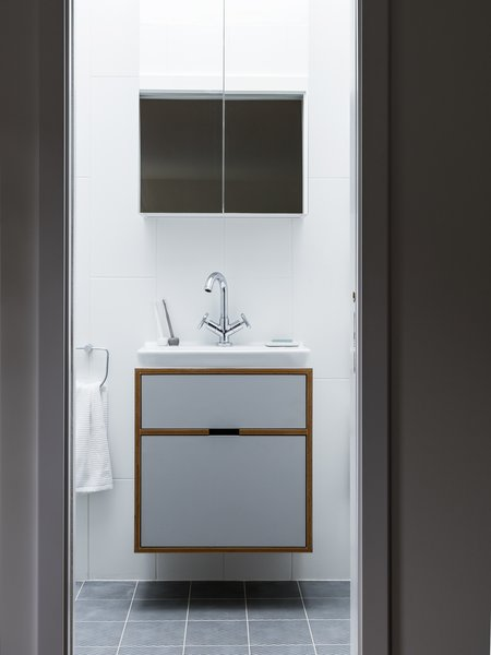 A floating bath vanity is composed of the same plywood detailing.