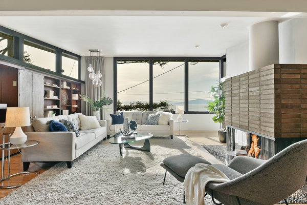 Built in wood shelving sits below clerestory windows, opposite a large brick fireplace with a sculptural chute.  Expansive windows provide views of the Bay beyond.