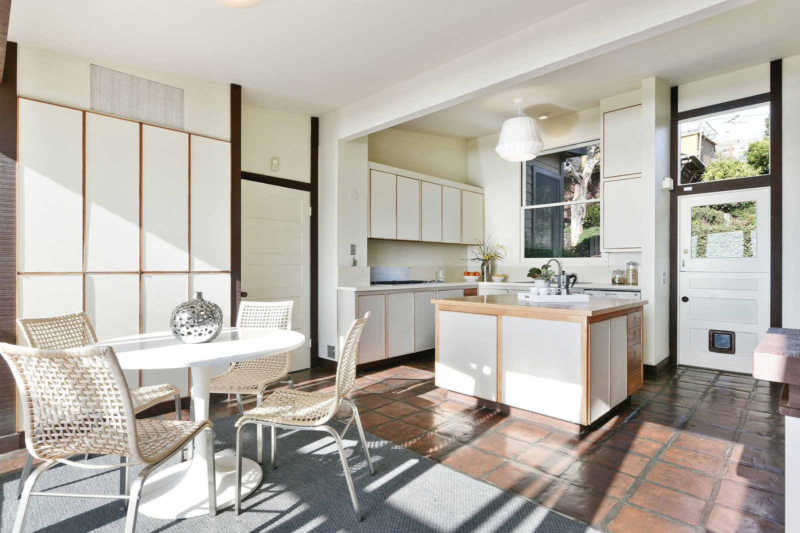 Kitchen, White Cabinet, Wood Cabinet, Pendant Lighting, Terra-cotta Tile Floor, Undermount Sink, Dishwasher, and Ceiling Lighting This kitchen was renovated in the late 1970s and has been beautifully maintained since.    Photo 6 of 14 in A Bay Area Jewel With Golden Gate Views Wants $1.55M
