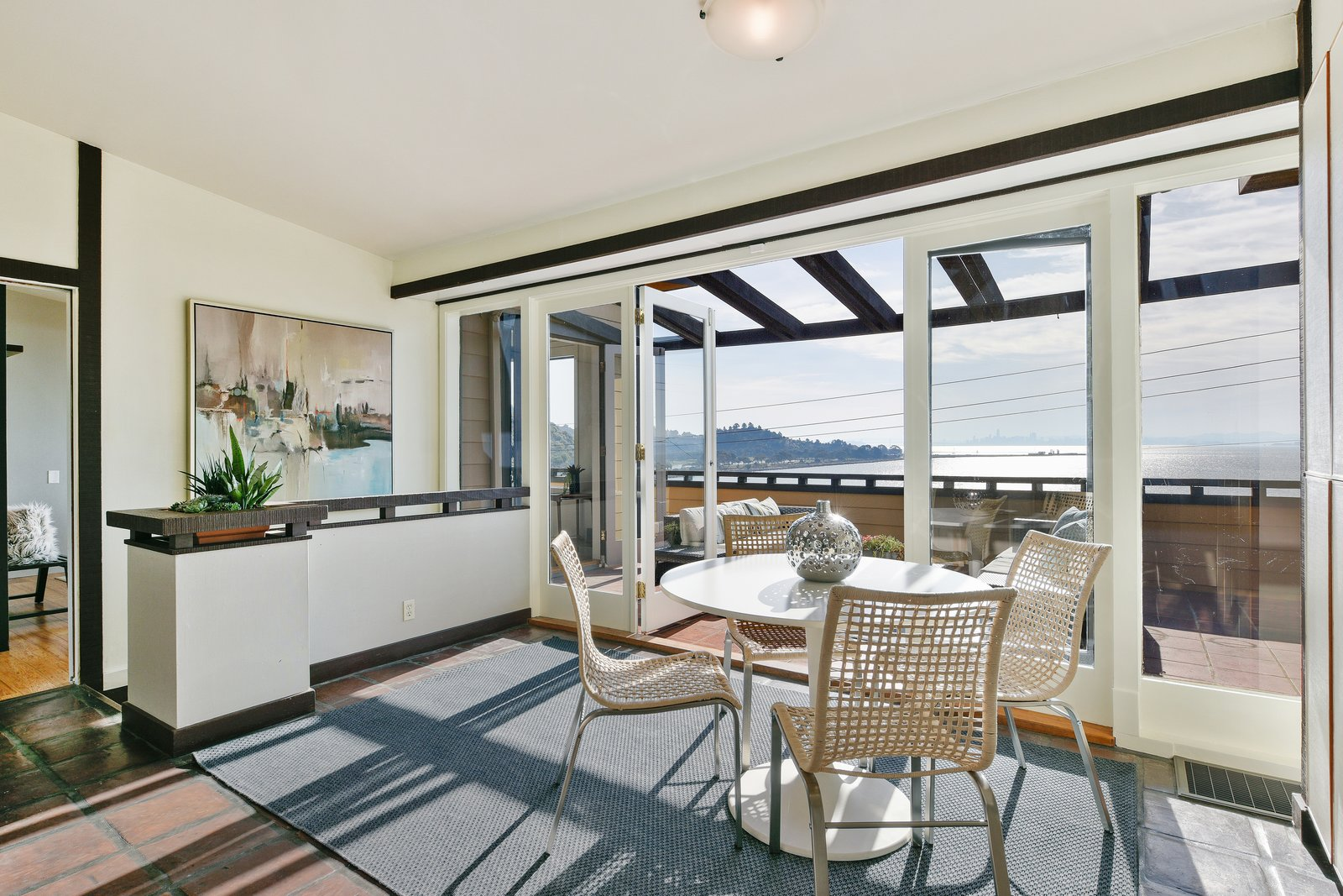 Dining Room, Ceiling Lighting, Rug Floor, Chair, and Table Full height glass doors allow the viewing terrace to blend seamlessly into the interior breakfast nook.  Photo 7 of 14 in A Bay Area Jewel With Golden Gate Views Wants $1.55M
