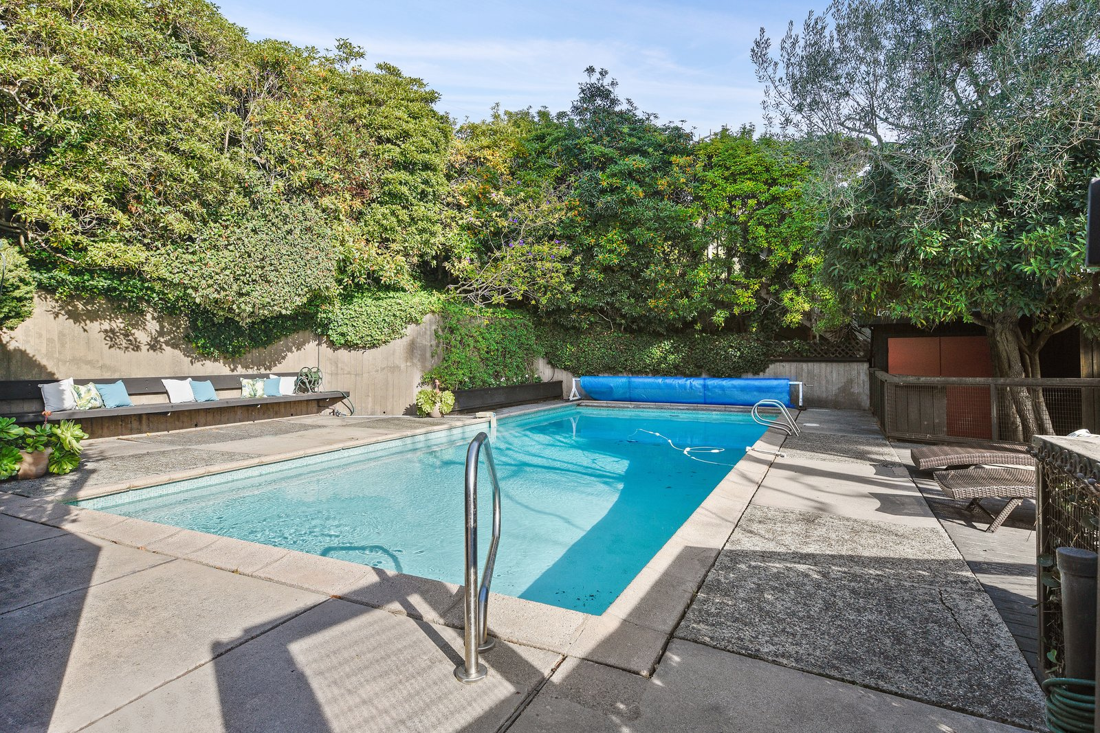 Outdoor, Concrete Pools, Tubs, Shower, Swimming Pools, Tubs, Shower, Concrete Patio, Porch, Deck, Vertical Fences, Wall, Trees, and Concrete Fences, Wall A solar heated pool is one of the many modern amenities that add to the iconic estate.  Photo 14 of 14 in A Bay Area Jewel With Golden Gate Views Wants $1.55M