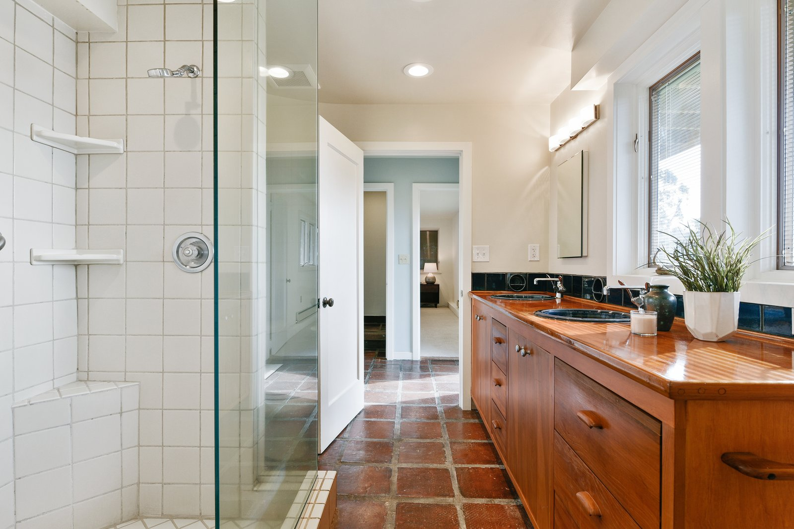 Bath Room, Corner Shower, Wood Counter, Vessel Sink, Recessed Lighting, and Wall Lighting A full bath with a double vanity and walk-in shower is accessible from both bedrooms on the lower level.  Photo 9 of 14 in A Bay Area Jewel With Golden Gate Views Wants $1.55M