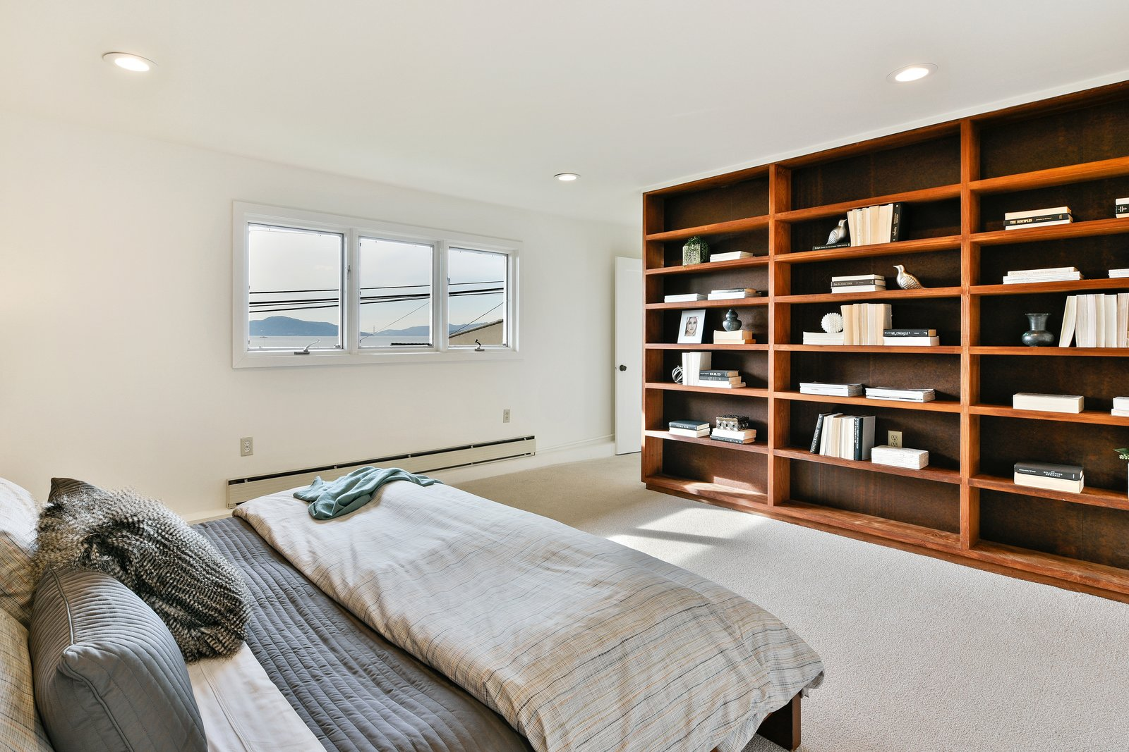 Bedroom, Bed, Shelves, Recessed Lighting, and Carpet Floor Built in bookshelves frame the Master Bedroom.  Photo 8 of 14 in A Bay Area Jewel With Golden Gate Views Wants $1.55M