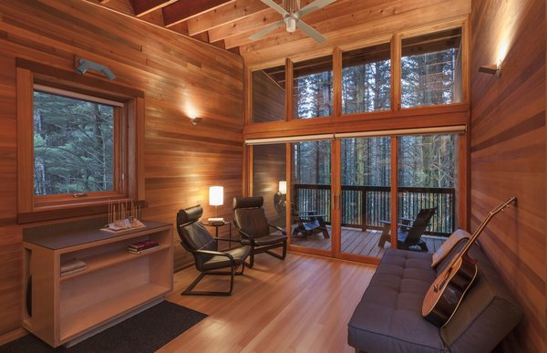 Cedar wood seamlessly extends from inside to outside, creating a continuous extension to the woods beyond.   Adirondack chairs provide the perfect viewing point from the balcony.