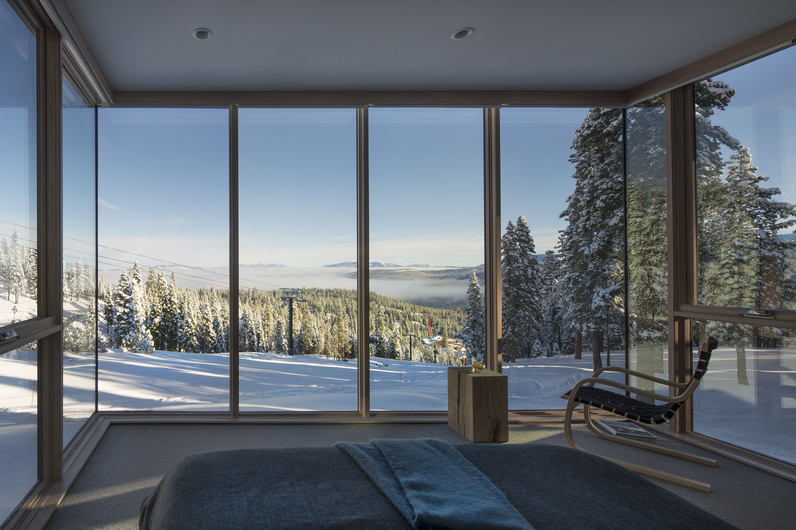 Bedroom, Carpet Floor, Bed, Chair, and Recessed Lighting Surrounded by glazing on three sides, the Master is a suite above the slopes, surrounded by nature.  Photo 8 of 11 in These Contemporary Lake Tahoe Chalets Have Ski-In, Ski-Out Access