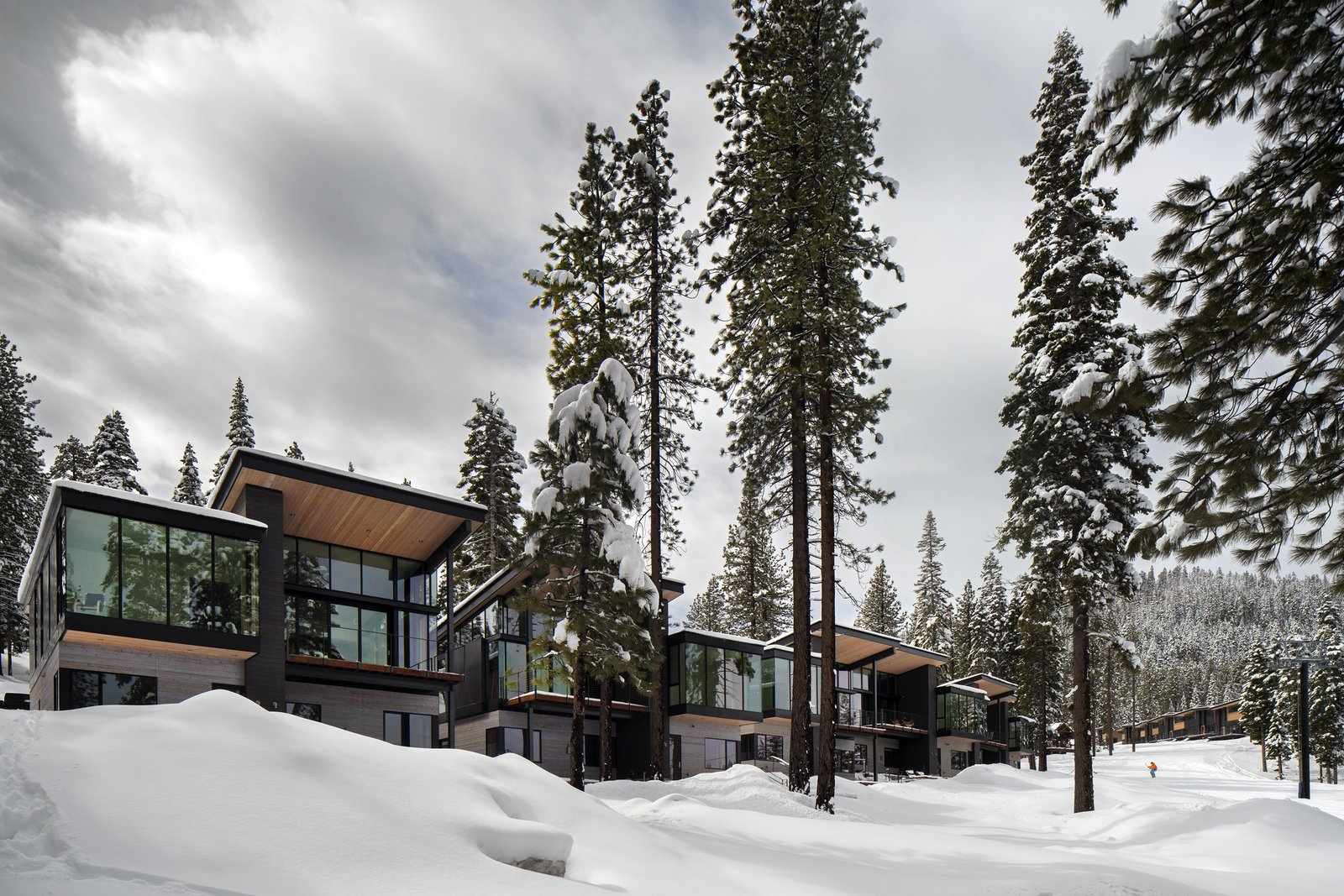 Outdoor, Trees, and Woodland Western Red Cedar, stained black, gray, and natural, wrap the facades of the Residences.  Roof canopies reach outwards to engage with the homes' setting.  Windows by Sierra Pacific provide incredible views of the surroundings.  Photo 9 of 11 in These Contemporary Lake Tahoe Chalets Have Ski-In, Ski-Out Access