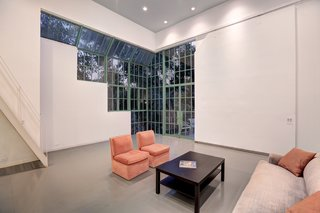 Large windows, panelized with green muntins,  frame the corner of the addition, providing views to the grounds beyond.