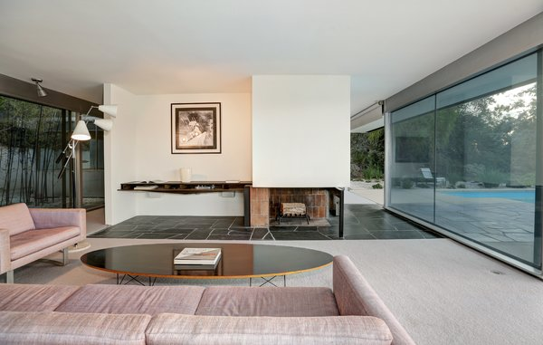 Mid-century modern furniture, including a Fat Chance Sofa and Chair, an Eames surfboard coffee table, and a Gino Sarfatti Triennale Lamp by Arteluce, decorate the living room.