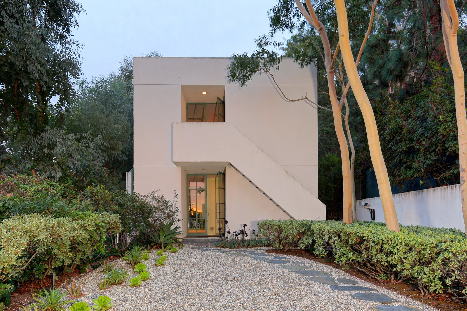 Exterior, Flat RoofLine, and House Building Type The two-story addition completed by Steven Ehrlich, FAIA,  is painted white and accented with green trim.   Photos from Richard Neutra's Stunning Loring House Is Listed For $5.6M