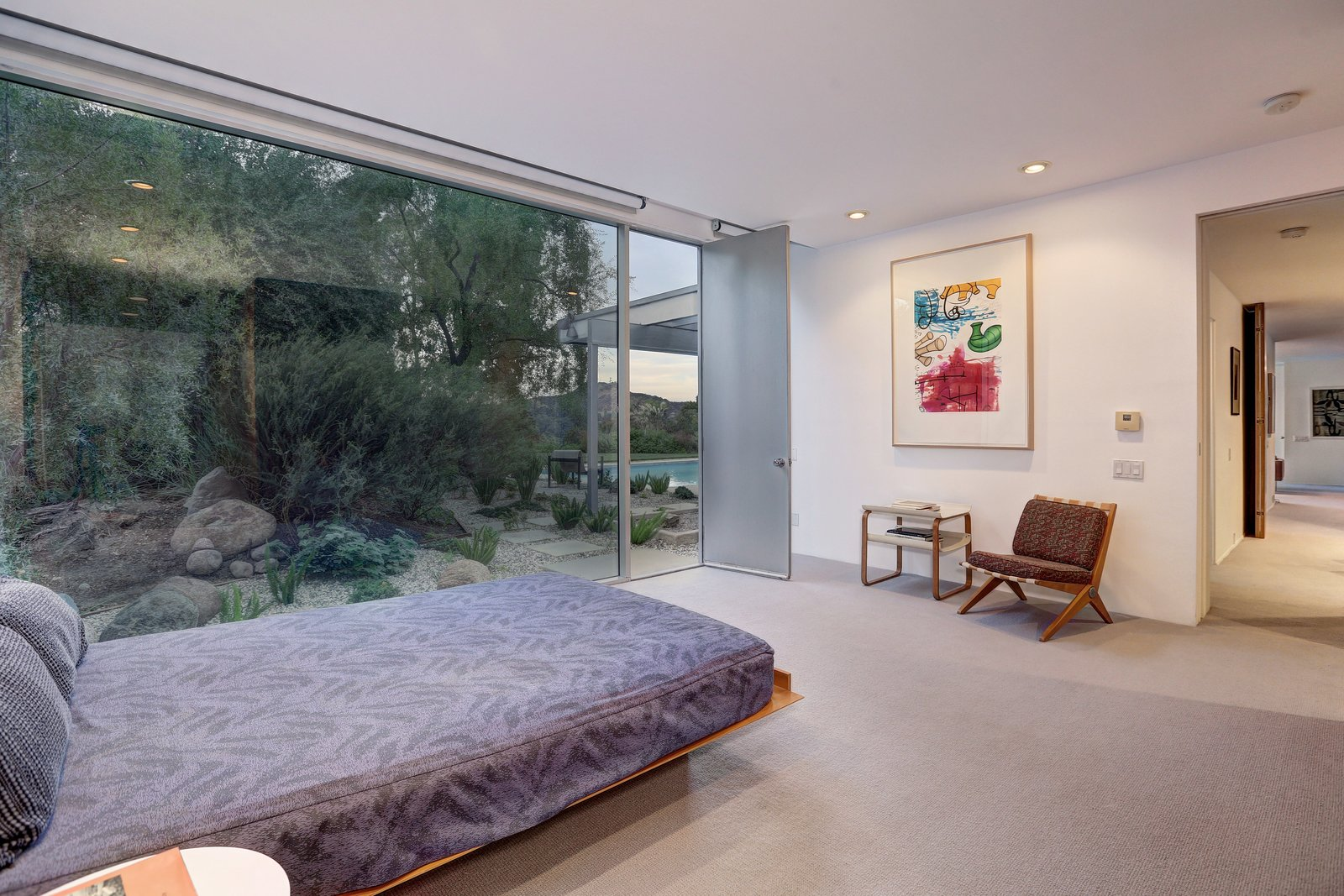 Bedroom, Chair, Carpet Floor, Recessed Lighting, Bed, and Night Stands The Master Bedroom addition completed by Escher GuneWardena, matches Neutra's original vision for expansion as shown in the archival plans.  A George Nelson influenced bed by Roberston + McAnulty looks onto the private gardens.   Photo 5 of 11 in Richard Neutra's Stunning Loring House Is Listed For $5.6M