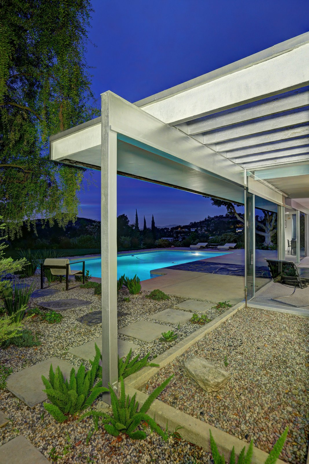 Outdoor, Walkways, Gardens, Side Yard, Swimming Pools, Tubs, Shower, Shrubs, Trees, Hardscapes, and Large Pools, Tubs, Shower Exposed structural members reach outwards and are painted a silver hue.   Photo 9 of 11 in Richard Neutra's Stunning Loring House Is Listed For $5.6M