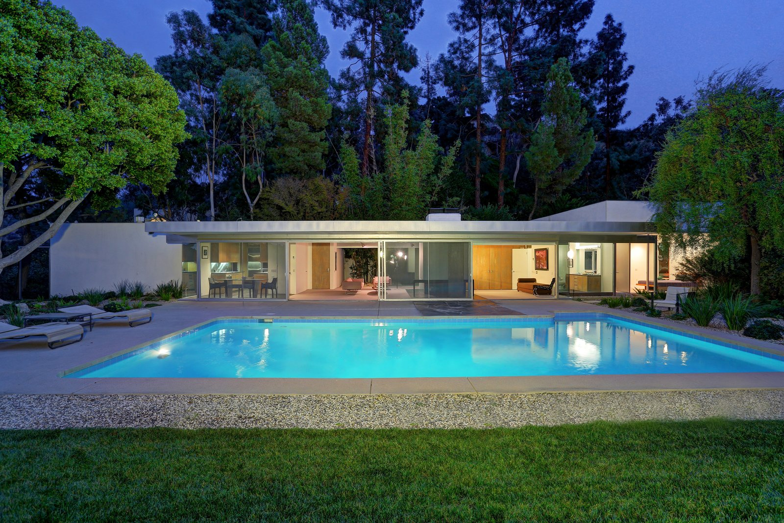 Exterior, Flat RoofLine, House Building Type, and Mid-Century Building Type At nighttime, the house glows as a mid-century modern icon.   Photo 7 of 11 in Richard Neutra's Stunning Loring House Is Listed For $5.6M