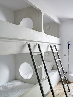 Custom bunk beds are built into one of the guest bedrooms.  A circular opening is a playful addition.