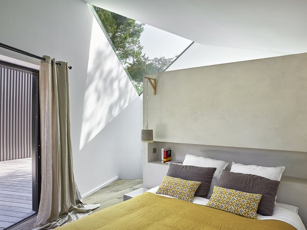 Triangular skylights make an appearance in the Master Bedroom as well.  A concrete partition wall with a recessed bookshelf provides a custom headboard solution.