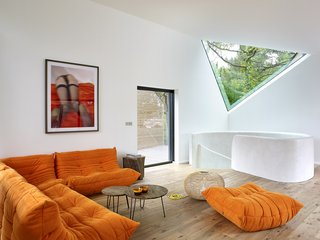 Designed by Atelier Du Pont, this breathtaking property exists in harmony with the surrounding landscape. Oriented in a manner that creates minimal impact on the existing terrain, the house idyllically nestles into nature, with vast views of the encompassing trees and vegetation. Inside, an orange Ligne Roset Sofa provides a comfortable space for rest and relaxation. A triangular window provides a picture of the tree canopy beyond, while drawing in natural light.