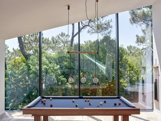 In the Game Room, slanted windows directly follow the roof line, creating a seamless connection.